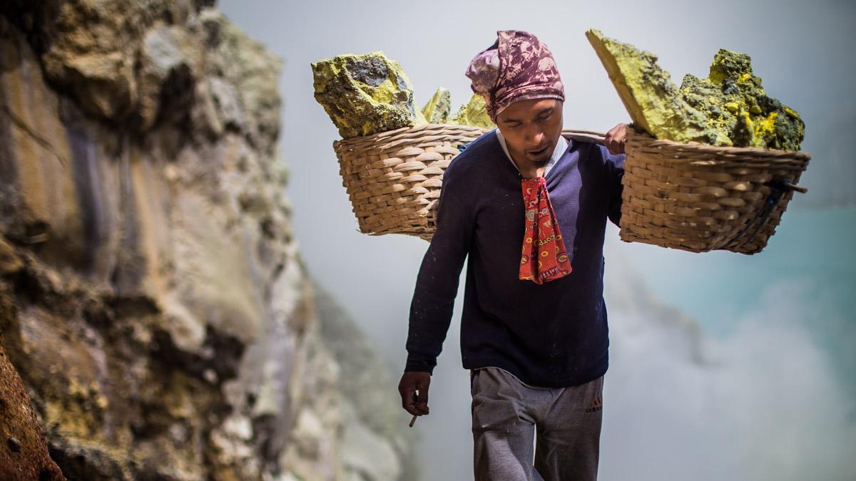 Travailleur de souffre dans le cratère du volcan Ijen
